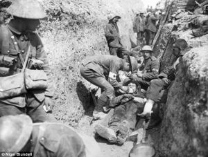 Royal Lancashire Fusiliers treating a wounded comrade in the Somme during the summer of 1916 during the First World War (c) Nigel Blundell.